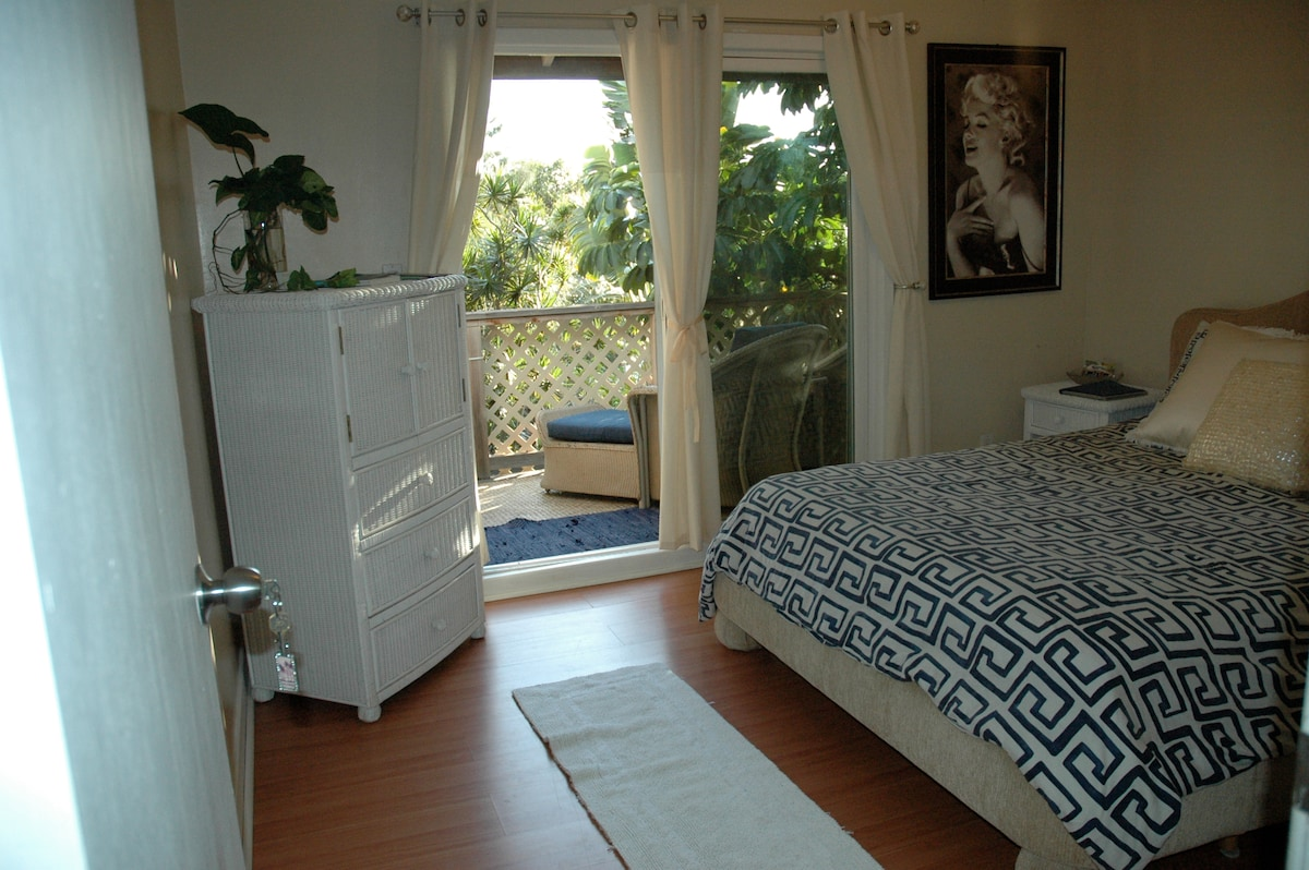 Updated picture of the room with new bed frame, curtains and patio furniture