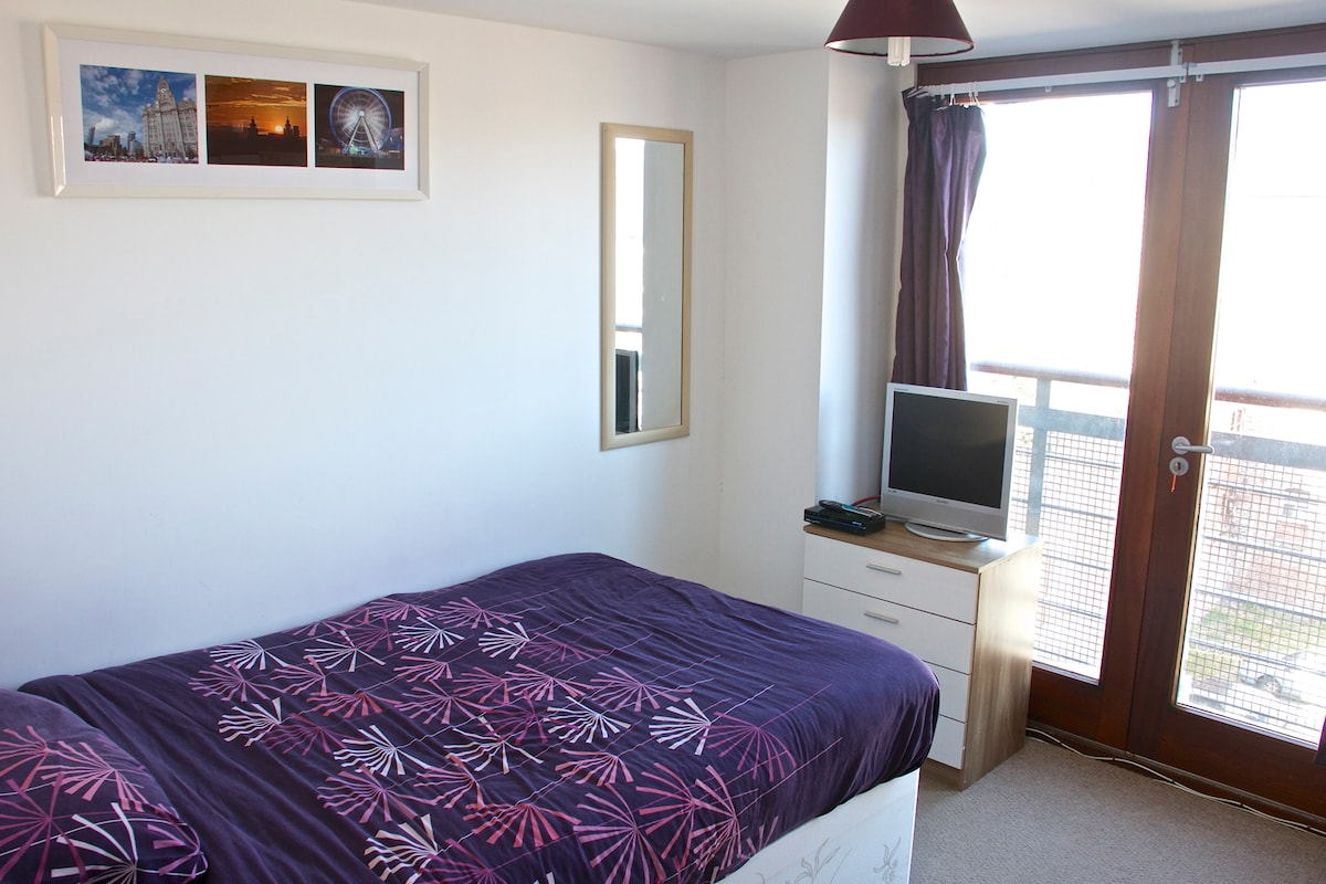 The Bedroom, complete with 4ft Double bed, TV, Bedside Cabinet with lamp, Chest of Drawers, Wardrobe, Mirror, & great views over Liverpool from the Double doors