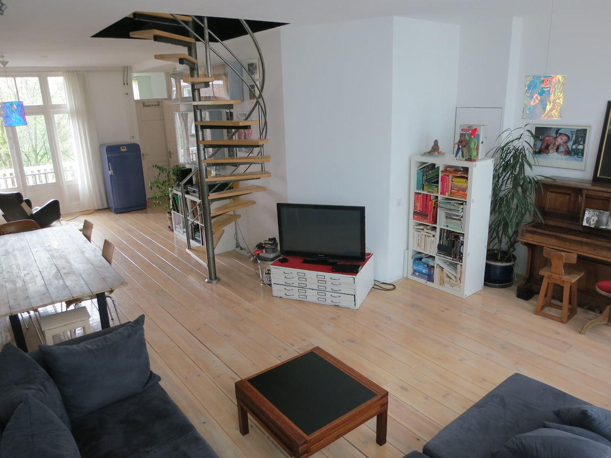 Spacious and bright living room with dinner table, flatscreen TV, books and a piano. The spiral staircase leads to the bedroom. Balconies on both sides of the room!