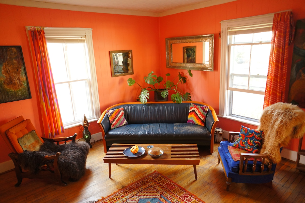 Living room, bright  with lots of windows and a selection of local paintings and sculpture.