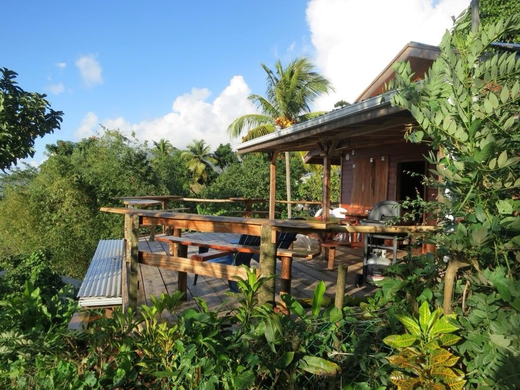 The Peanut Farm Bungalow opened in December 2013 and is designed using all local Island wood and Stone. Nestled on a hillside near Portsmouth the bungalow is located in a peaceful rainforest setting above Ross Medical School.