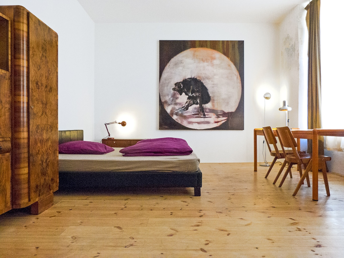 XL Bed, vintage furniture and original art in a large loft room.