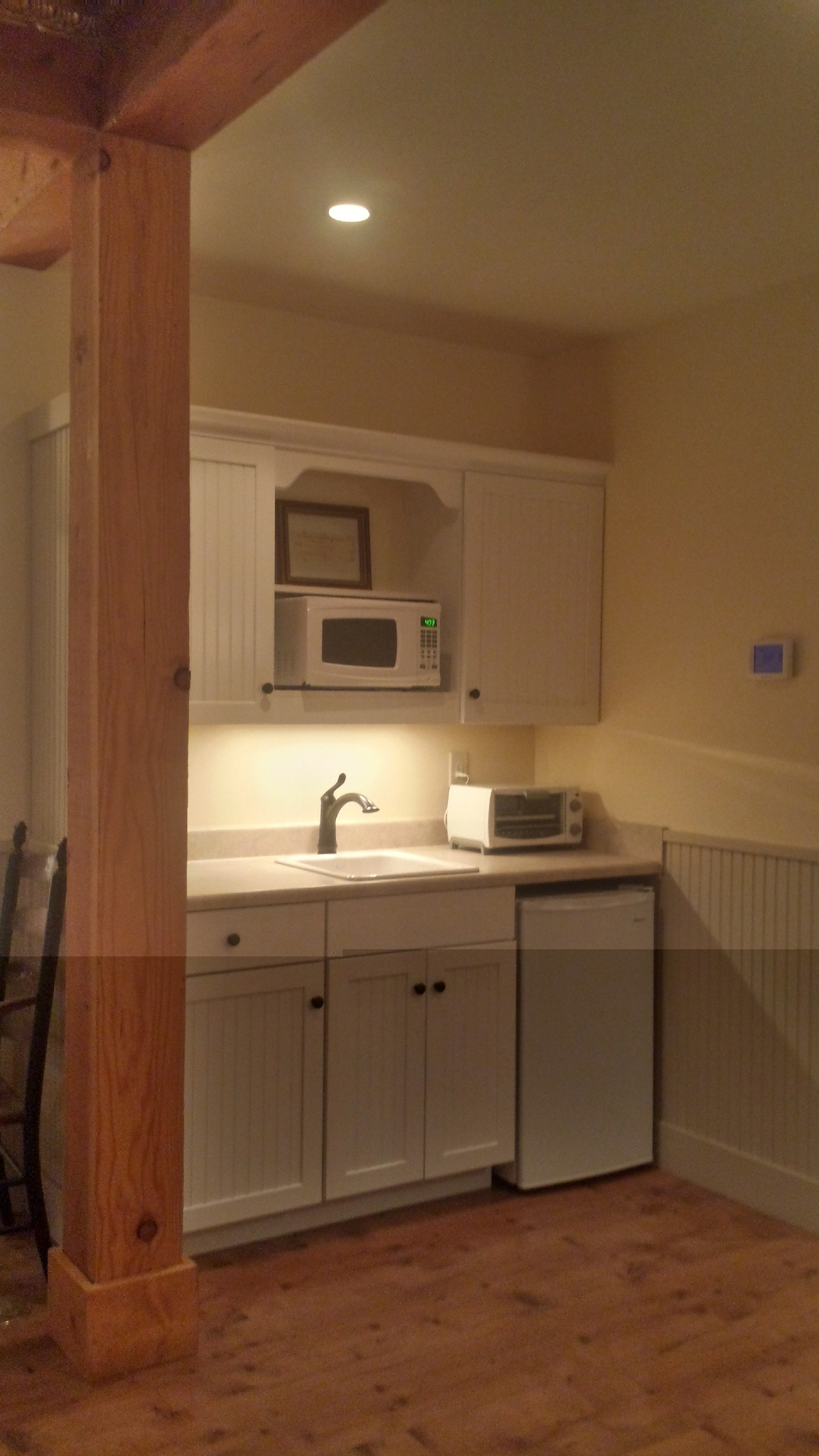 Kitchenette with microwave, coffee maker, toaster oven and small refrigerator.