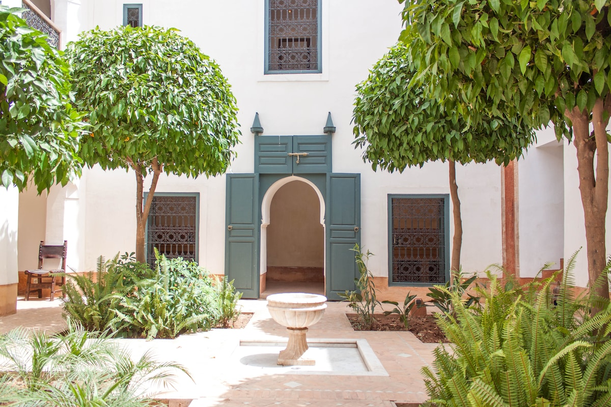Central courtyard with marble fountain and orange blossom trees.