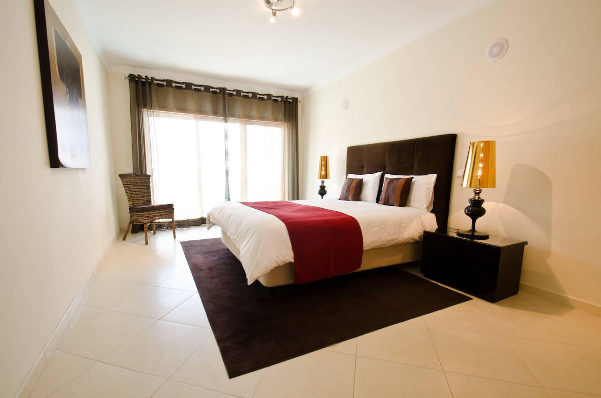 Contemporary bedroom with fitted wardrobe and ensuite leading to spacious balcony with sun loungers