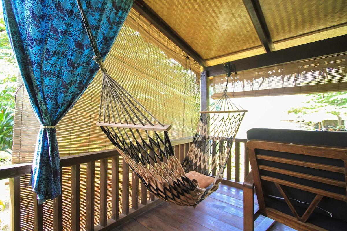 Read, nap, dream on the verandah hammock of an authentic 90 year old Malay Farmers' Hut!