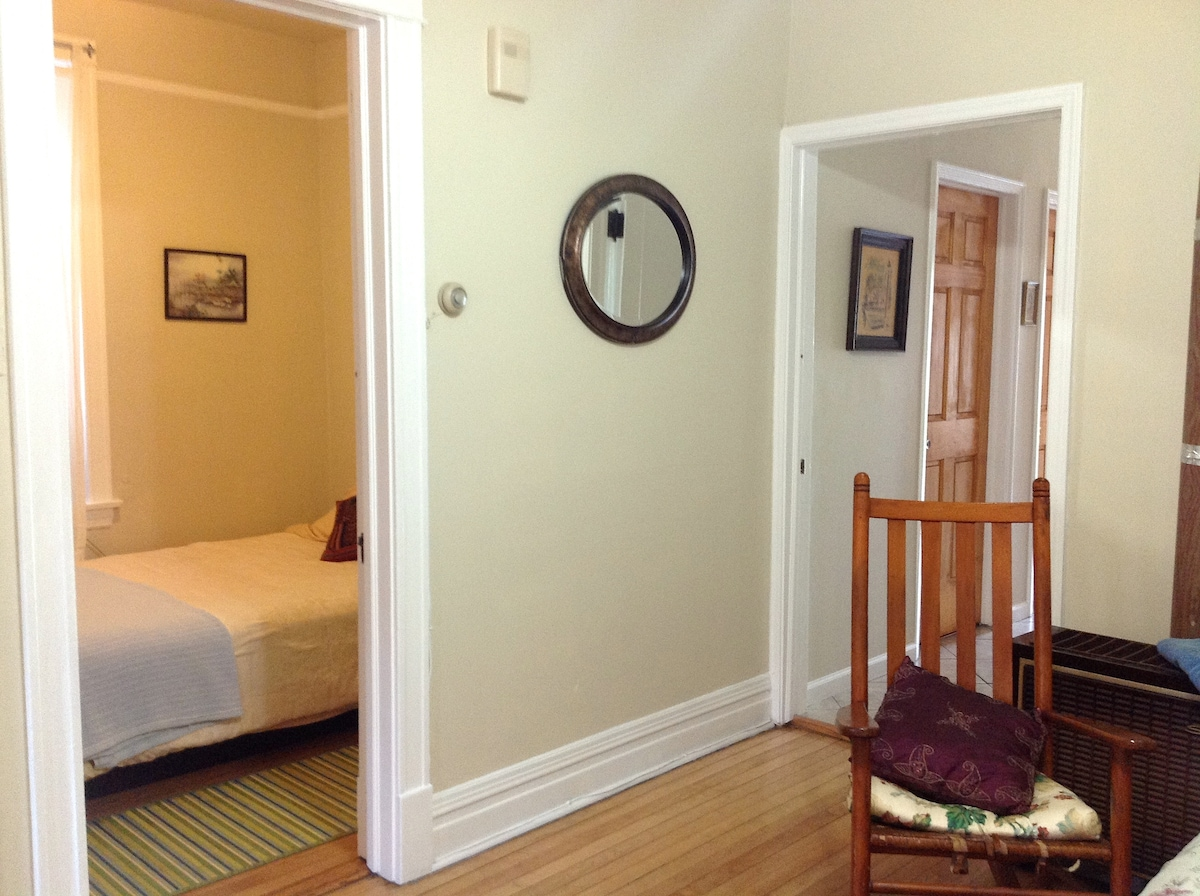 A smaller bedroom with a full bed opens up on the main bedroom/living room.