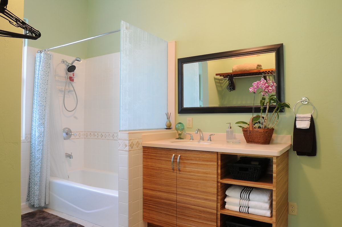 Newly remodeled bathroom with a zebra wood vanity with solid surfaace countertops