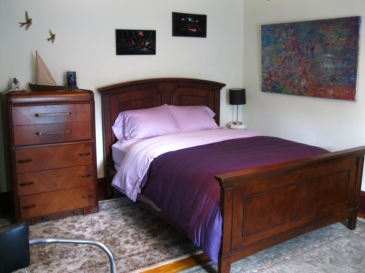 The front bedroom. Large and sunny. Queen-size bed. Solid french doors to living room.