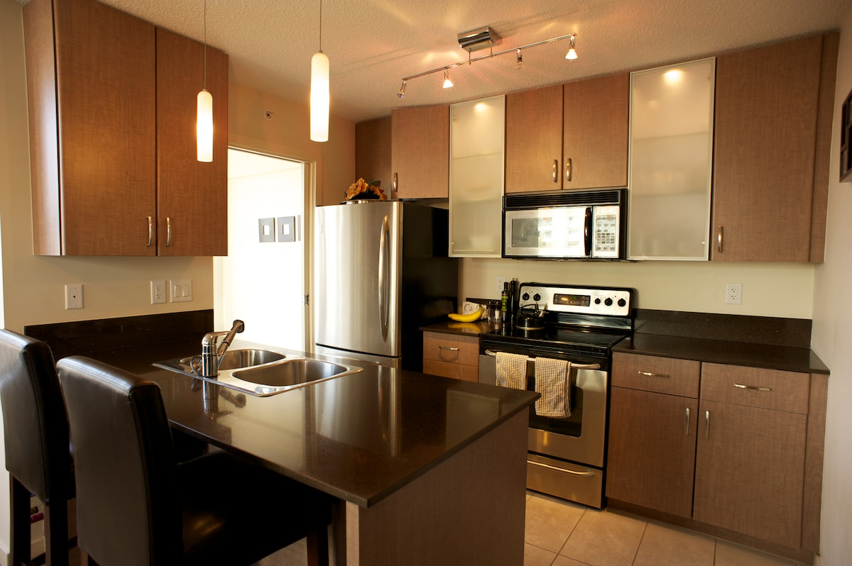 Fully equipped kitchen with European style full height cabinets, dishwasher, smoothie machine, plates, cutlery, microwave, oven etc