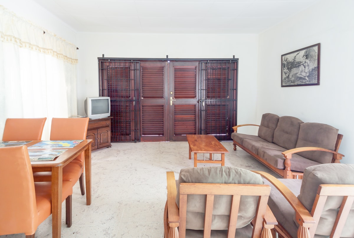 Spacious living area with comfortable sofa, armchairs, dining table and chairs