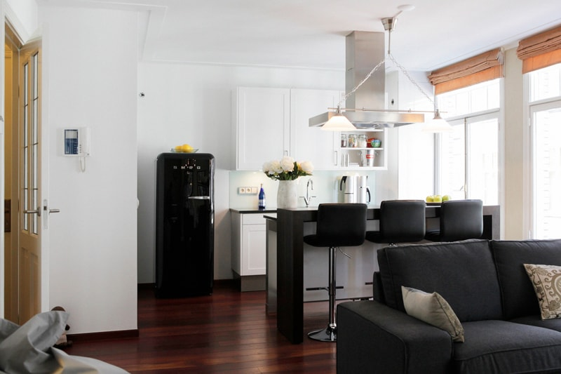 The modern kitchen with a cooking island and bar is fully equipped.