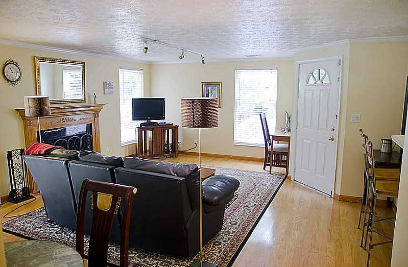 Spacious living room with leather couch, TV (cable, WiFi), wood fireplace with gas starter.