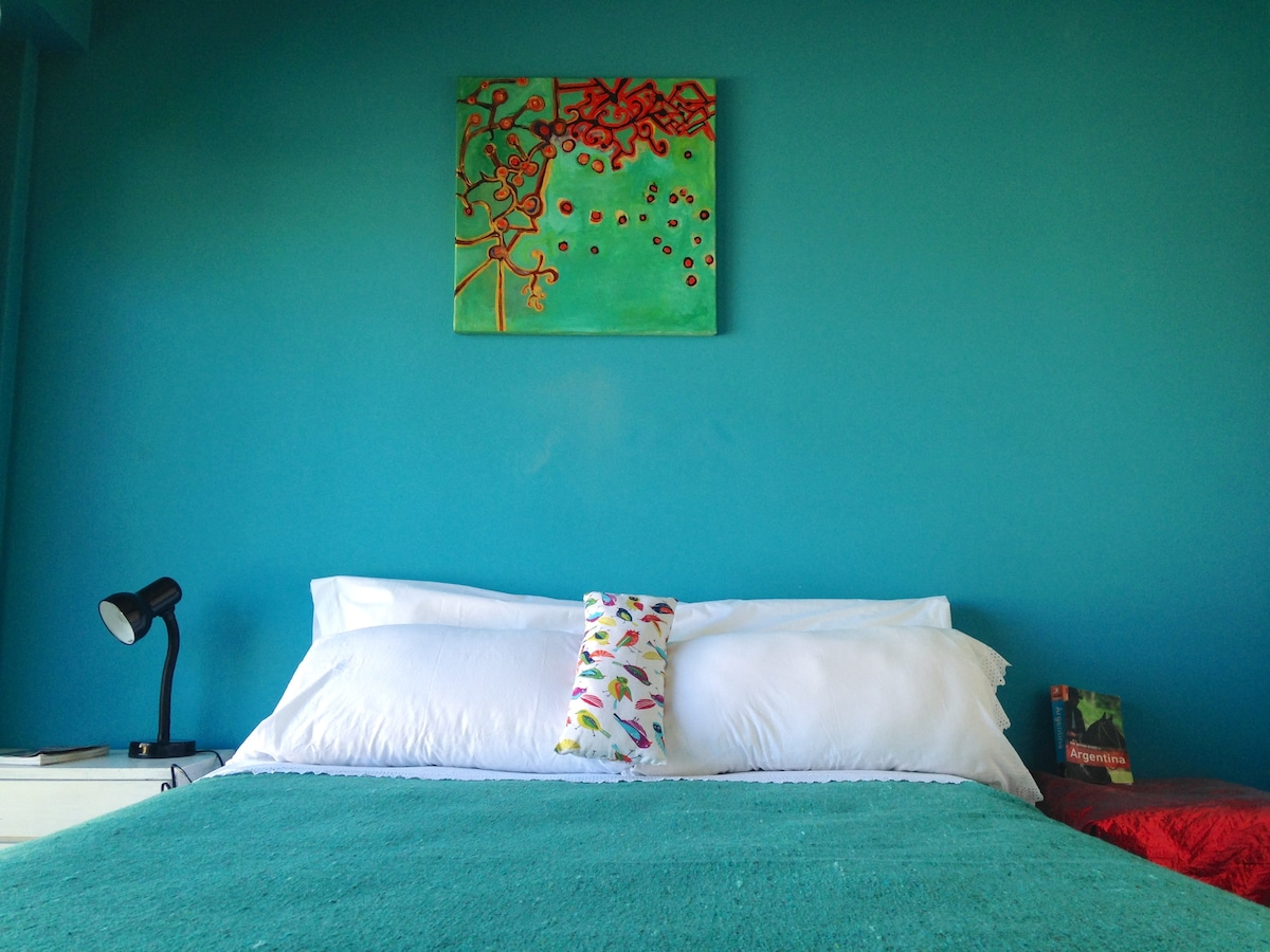 Colorful and super comfy bedroom with original paintings