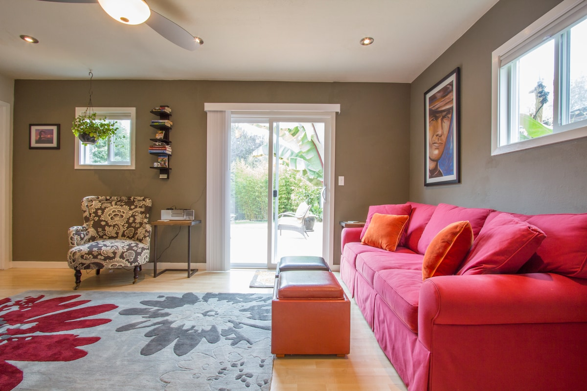 Living room - open and airy with plenty of natural light. Back patio and yard through the sliding door.