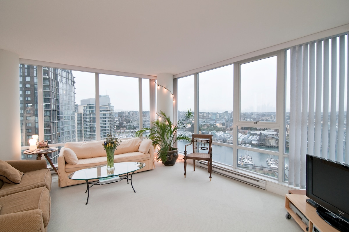 Shared living room with flat screen, music system and views over false creek.