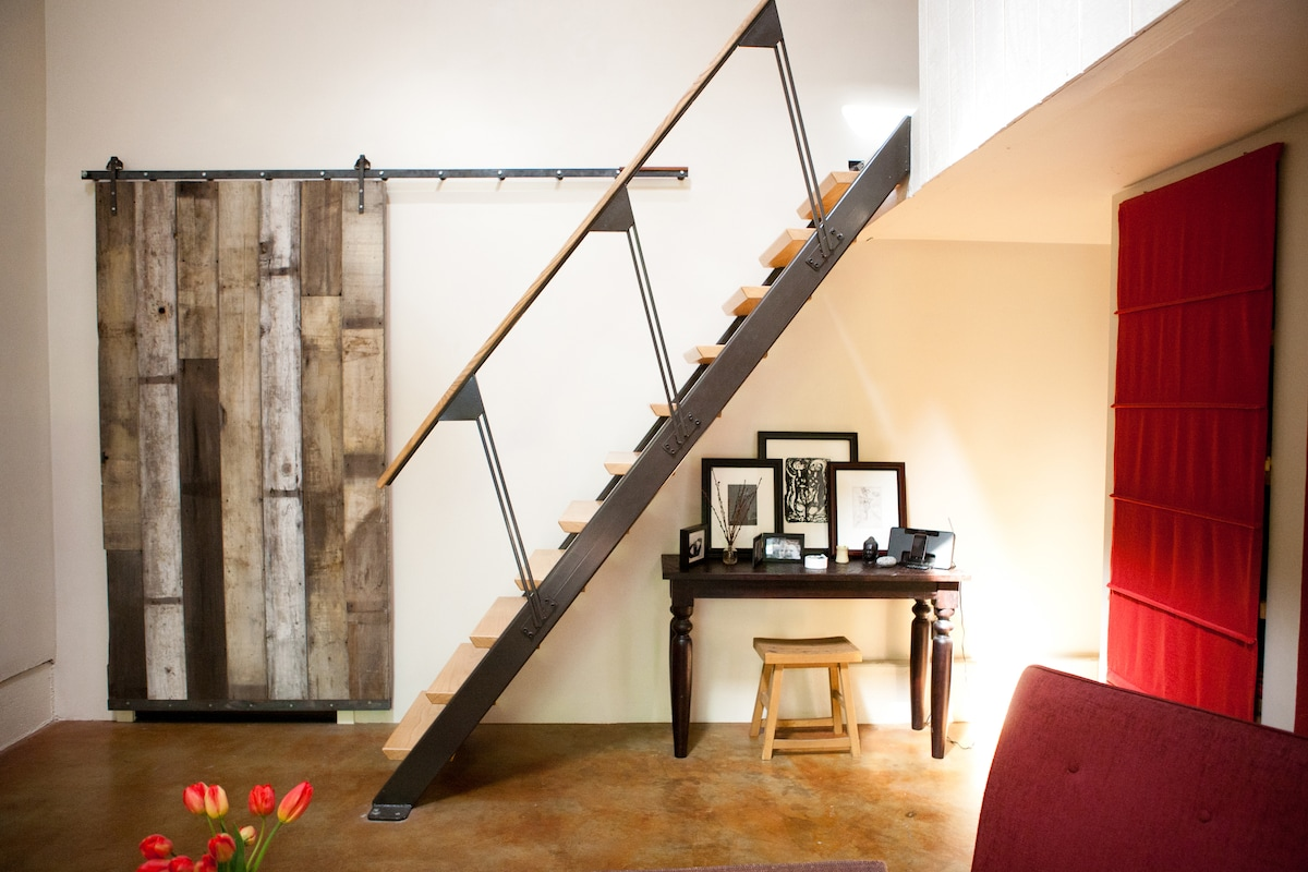 Reclaimed wood barn door and steel and oak hand forged staircase to loft bedroom