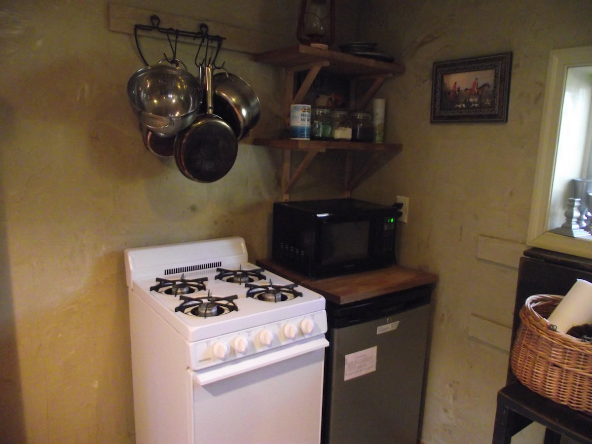 Gas stove, mini fridge, microwave, pots, pans and the ever important coffee.