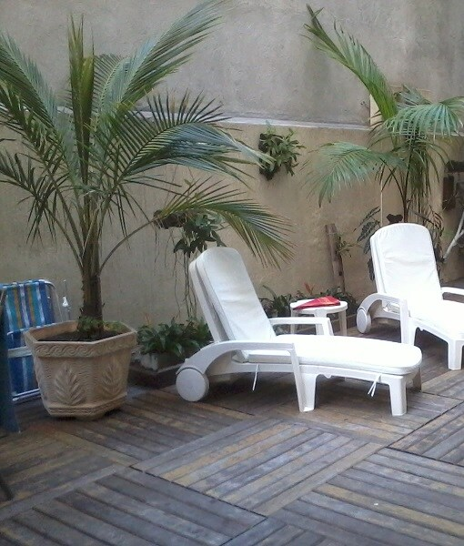 Garden furniture. Beach towels and chairs. Tropical plants