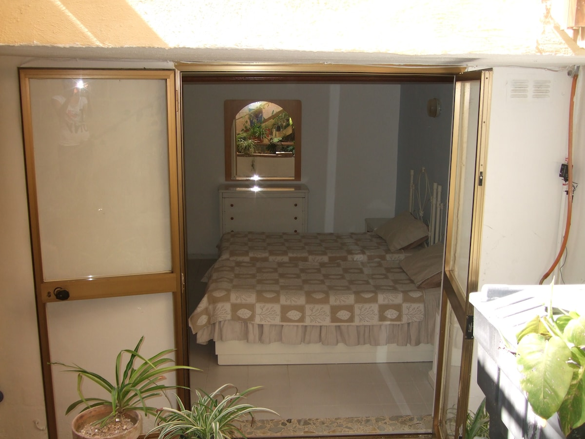 bedroom with 2 single beds overlooking an internal yard with fish pond