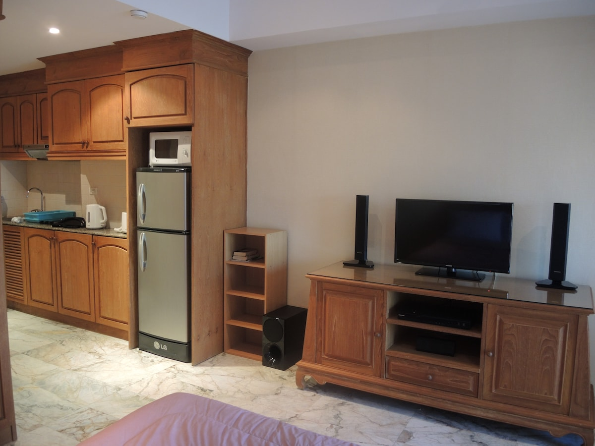 A compact but fully equipped kitchen with Fridge/freezer, Microwave oven, A modern Ceramic 2 hob cooker. All in teak wood furniture