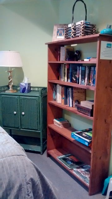 Bookcase with books, magazines, games and DVDs.