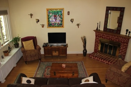 This is a view of the bright living room with French windows facing the sycamore-lined street.