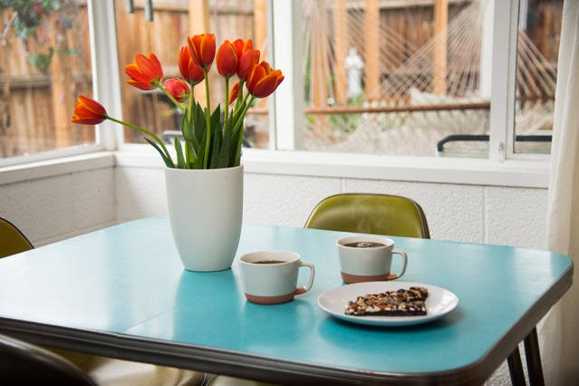 Sip your morning tea with a view of the garden from a Vintage dining table with Eames chairs straight (from SHIPS Coffee Shop in Culver City.)