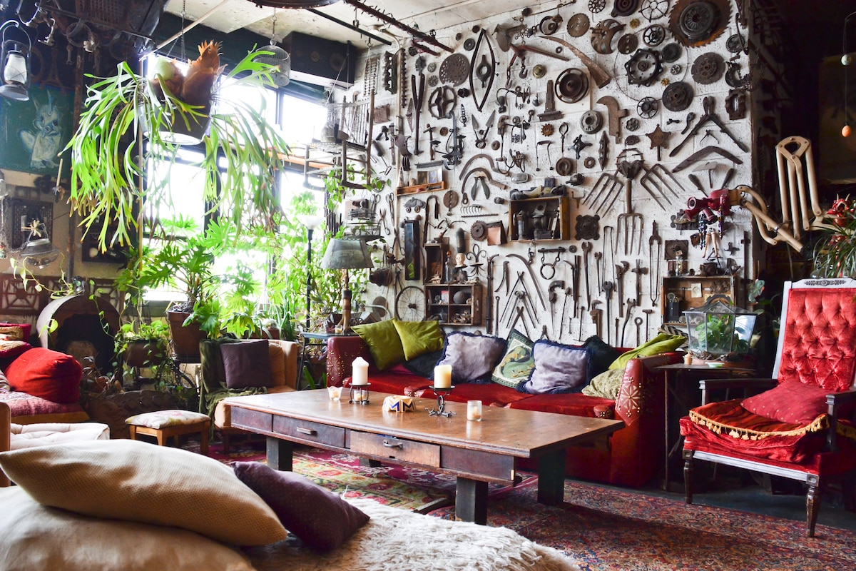 The Living Room, featuring the wall of tools, custom jueged red velvet couch, throne & plants galore. South facing windows with a view of the Williamsburg Bridge.