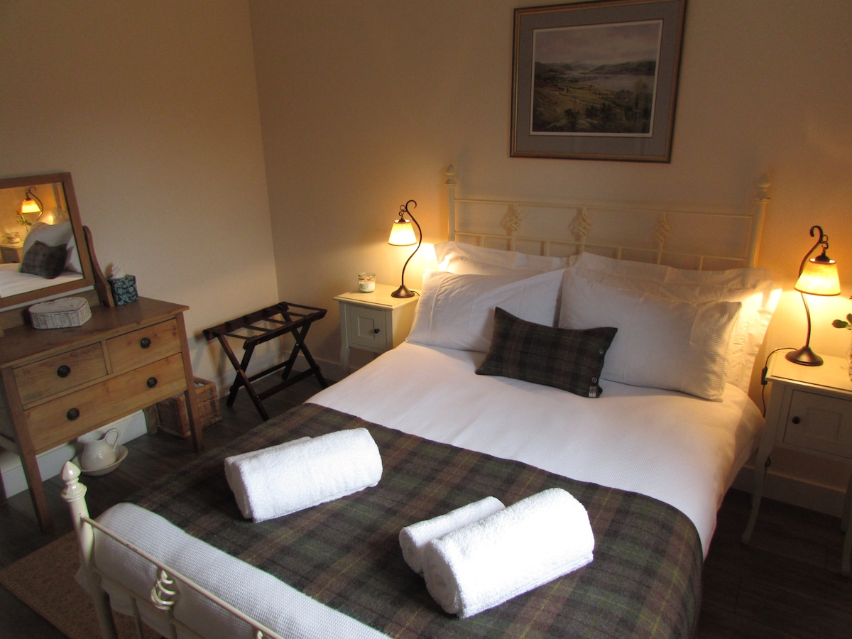 The bedroom has a double bed,  wardrobe, white linen and big fluffy towels.