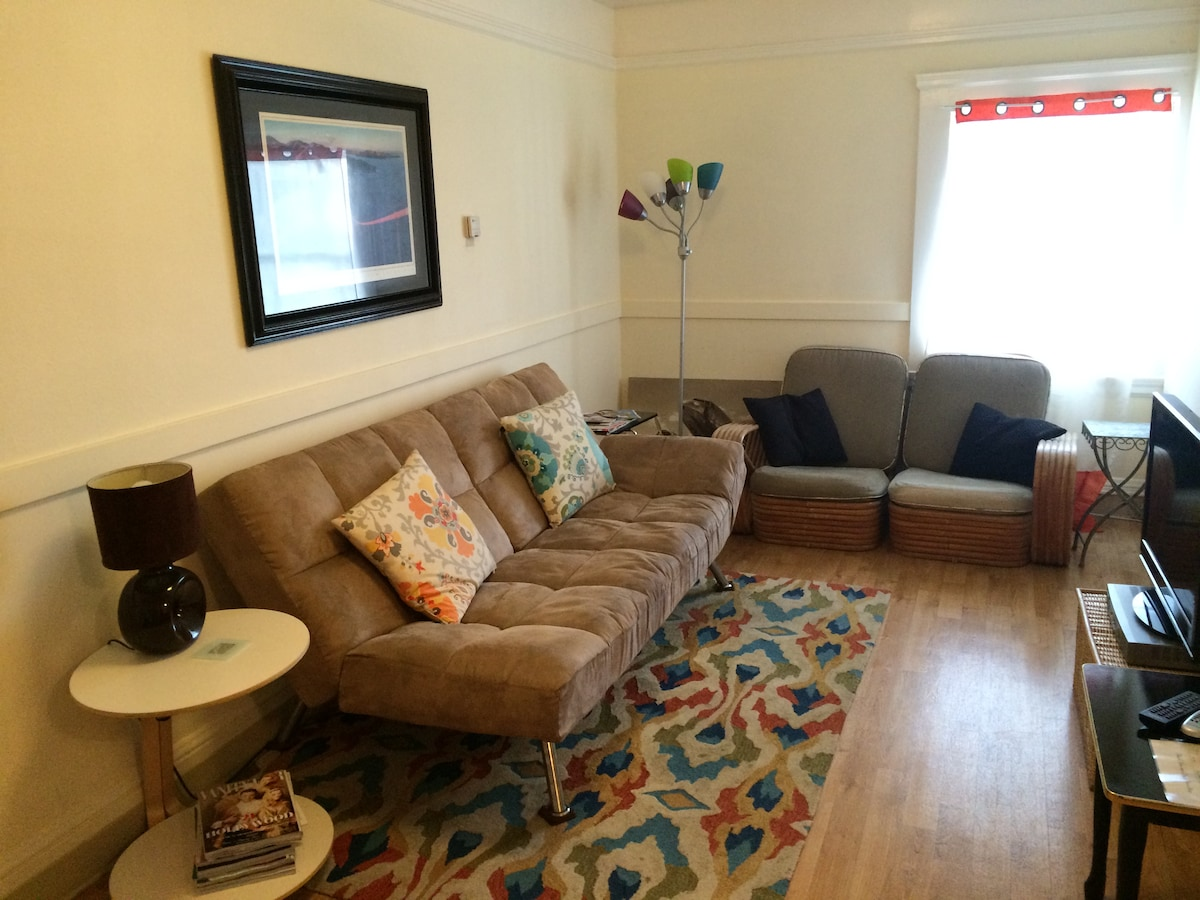 Comfortable living room with convertible sofa, ample seating a cable TV.