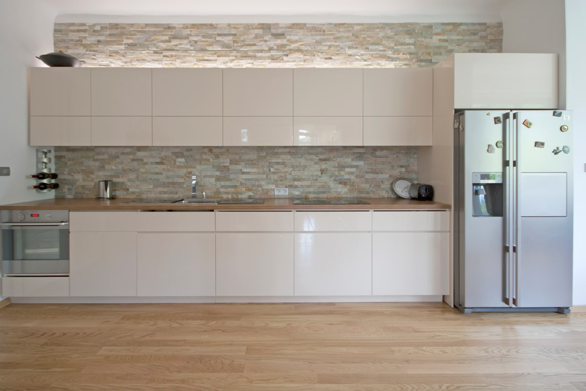 Kitchen with oven, sink, dish-washer, induction plate and american.-style refrigerator.