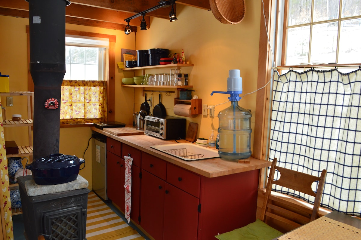 kitchenette with fridge, bottled water over sink, induction cooktop, cooking and eating utensils