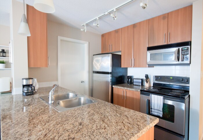 Kitchen with granite counterops, stainless steel appliances (range, stove, fan, microwave, dishwasher is under the granite counters)