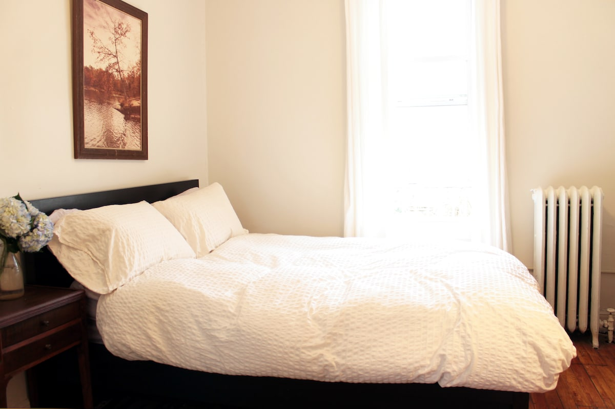 Your sunlit guest room with a full bed