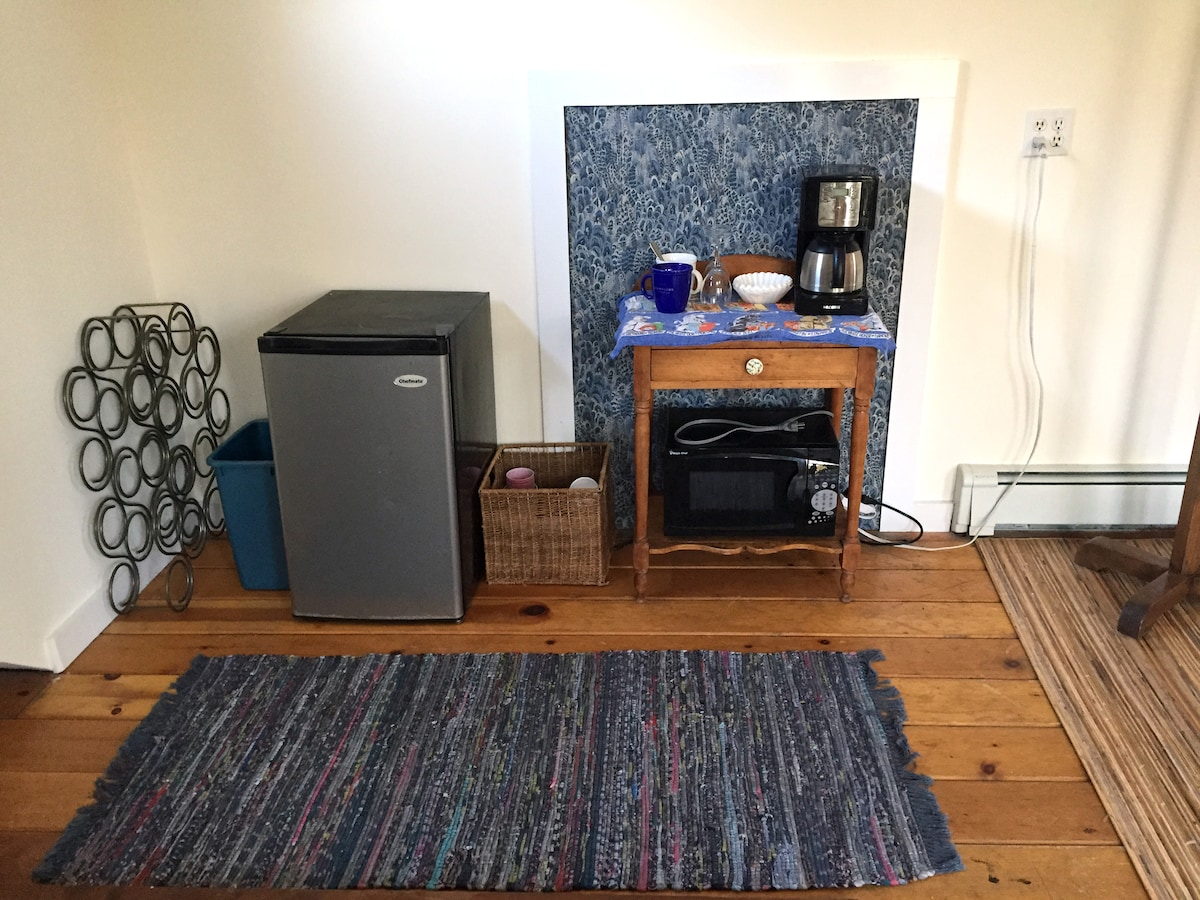 Small kitchenette provided with coffee maker, fresh coffee, tea, milk, microwave, brita pitcher, mini-fridge and dishes.