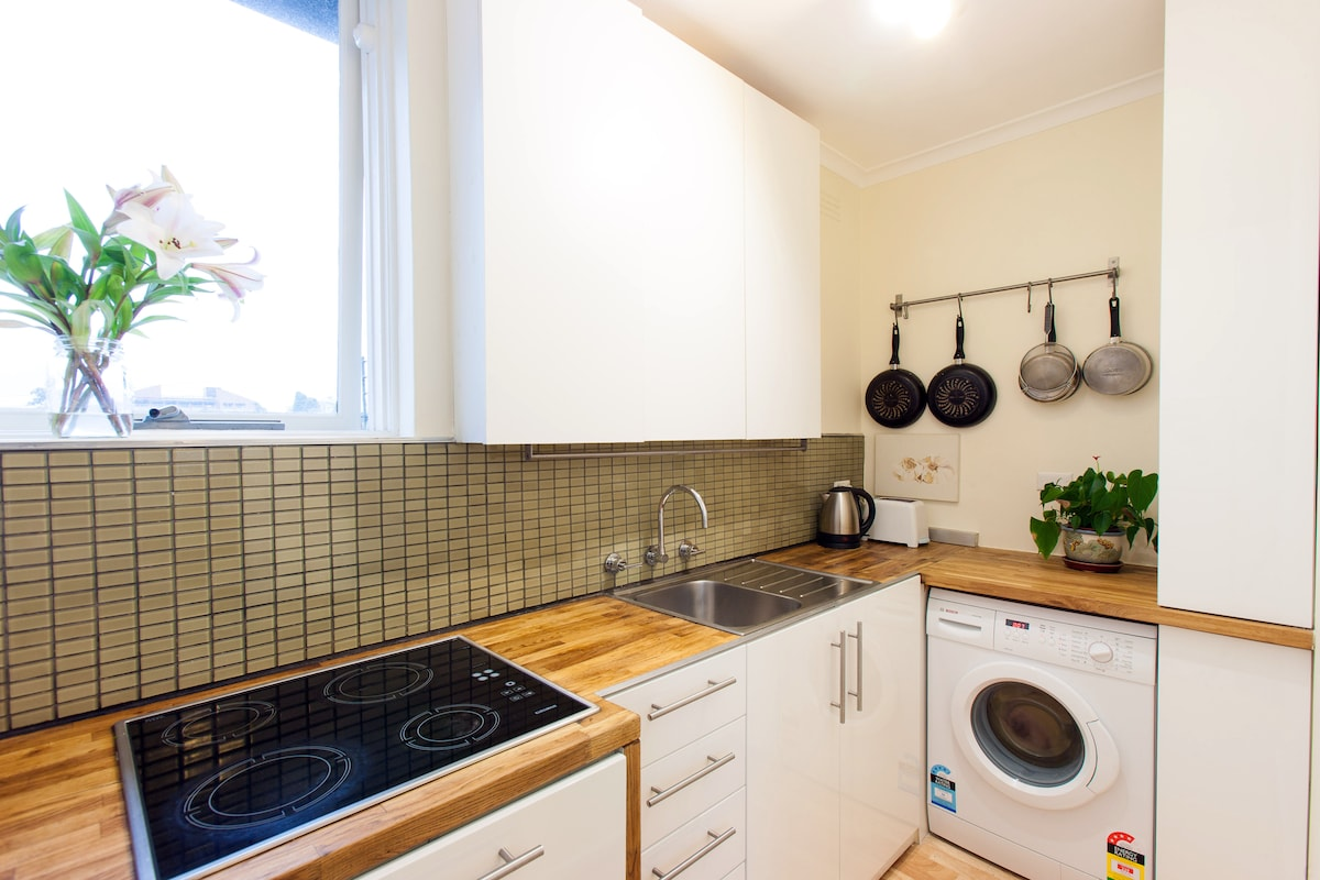 You'll enjoy cooking in this compact kitchen. The dishwasher is located below the electronic stove top. The washing machine is located at the right, beside the cupboards where we store our cleaning materials.