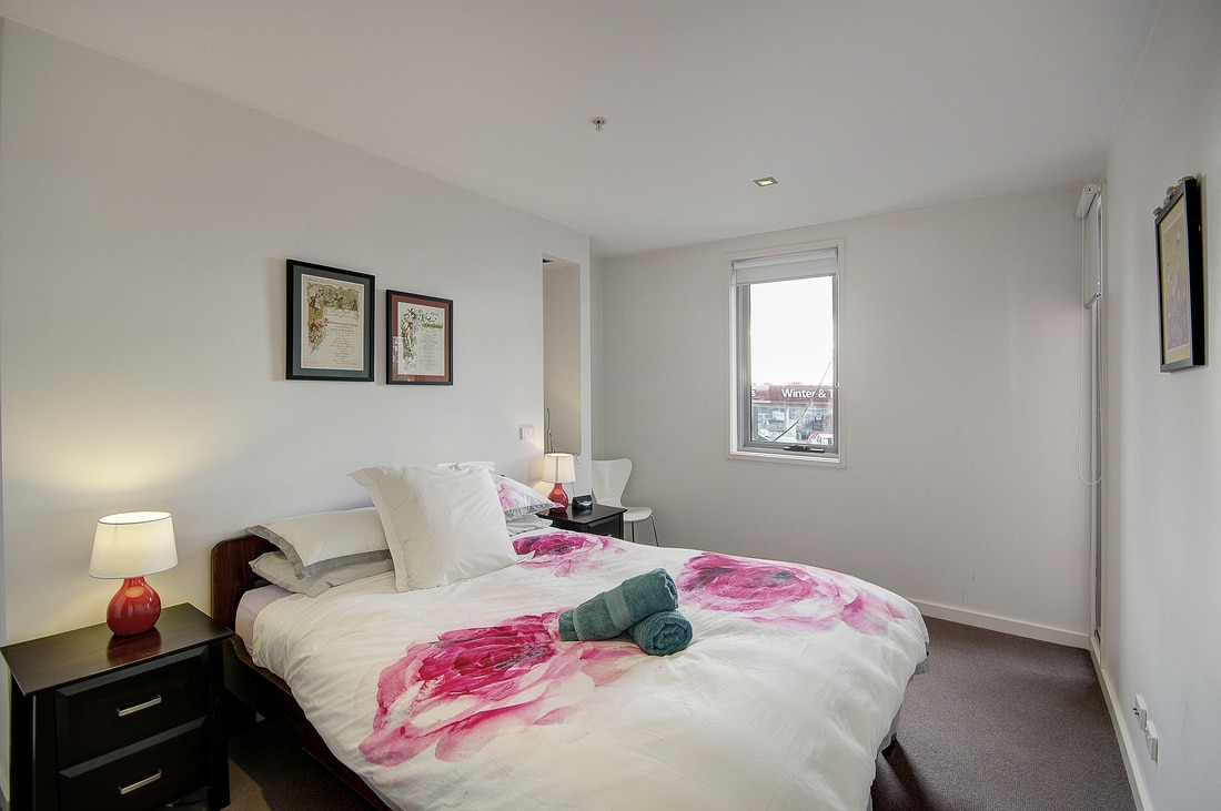 The main bedroom has a queensize bed, side tables and lamps. {there is room enough for a child to sleep on the spare single mattress.