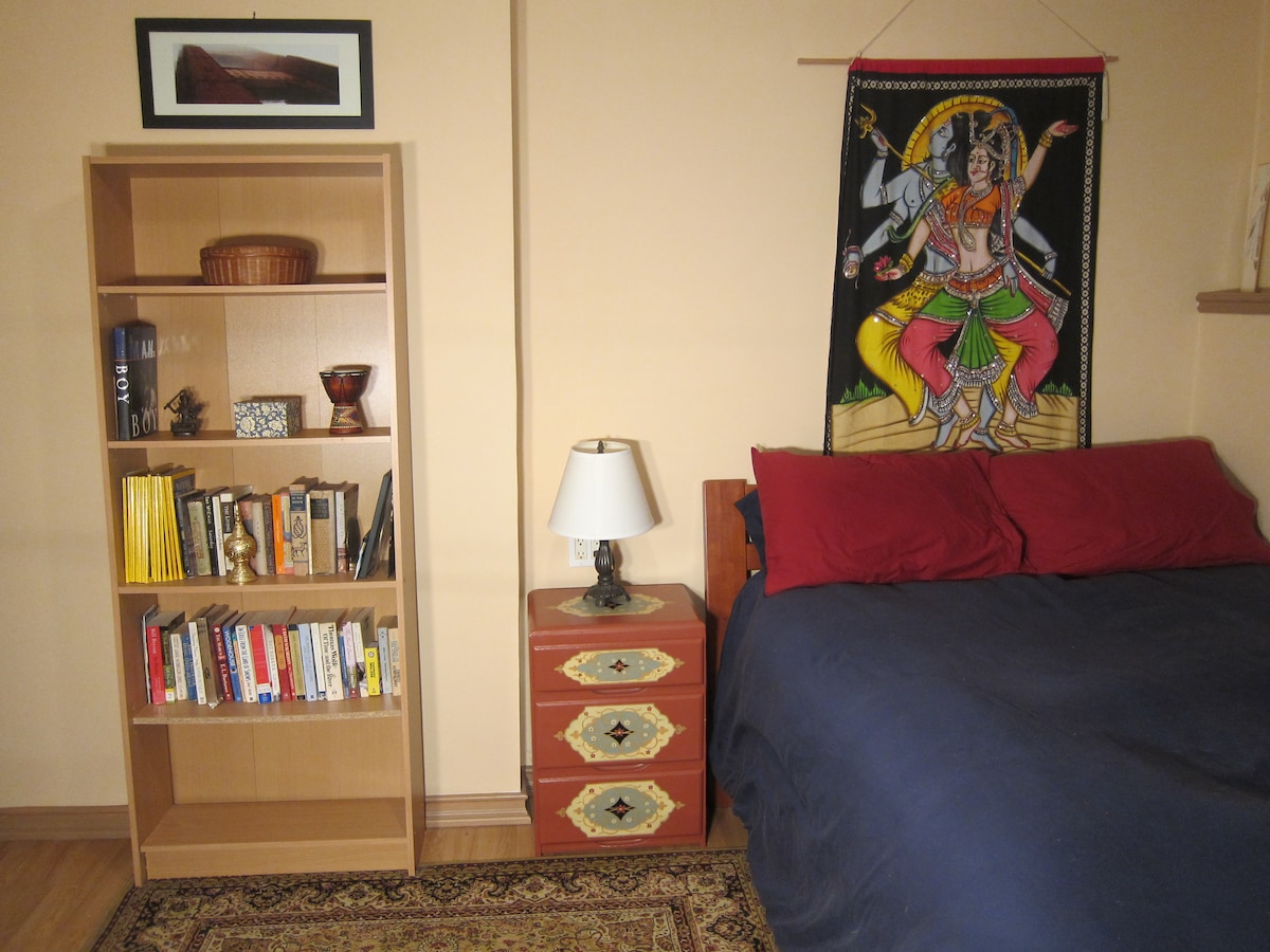 Super comfy bed with a bright and cheery Indian wall hanging.