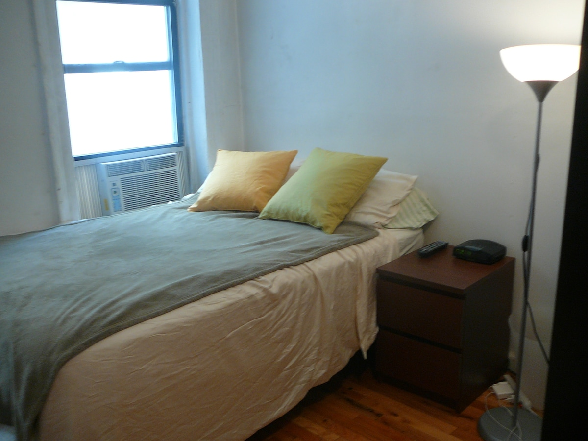 Primary bed with A/C and nightstand next to the bed