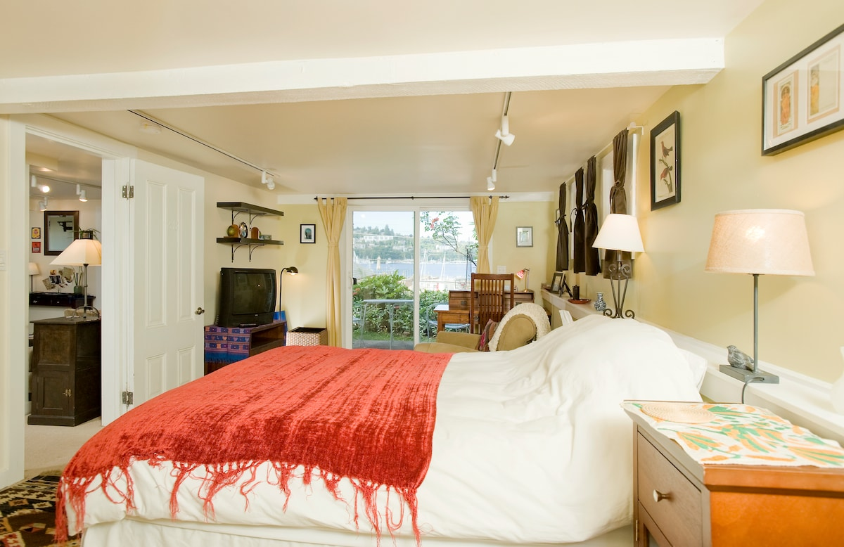 The large bedroom has sliding doors that open onto a patio with a view onto Lake Union.