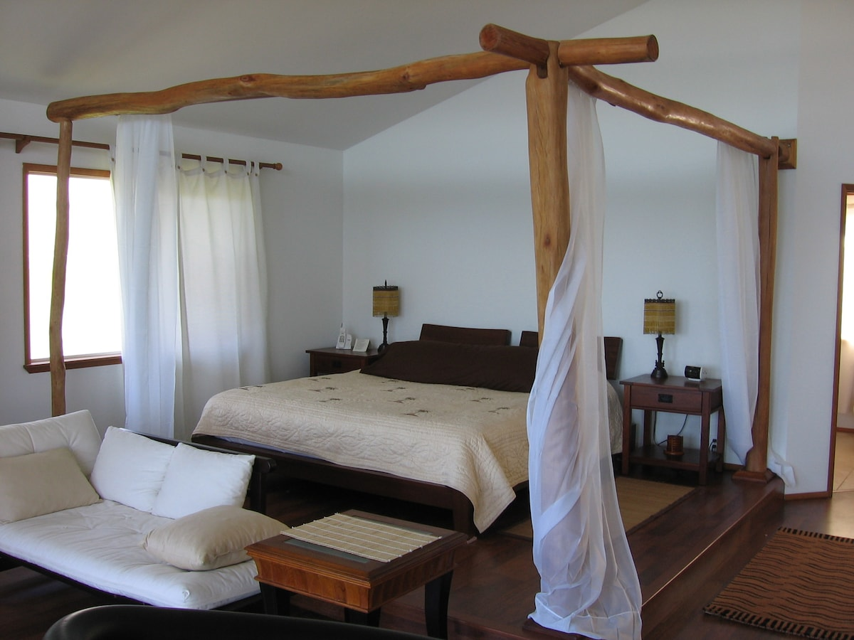 Romantic master bedroom suite with canopied king size platform bed, facing the sea at Hale Mar