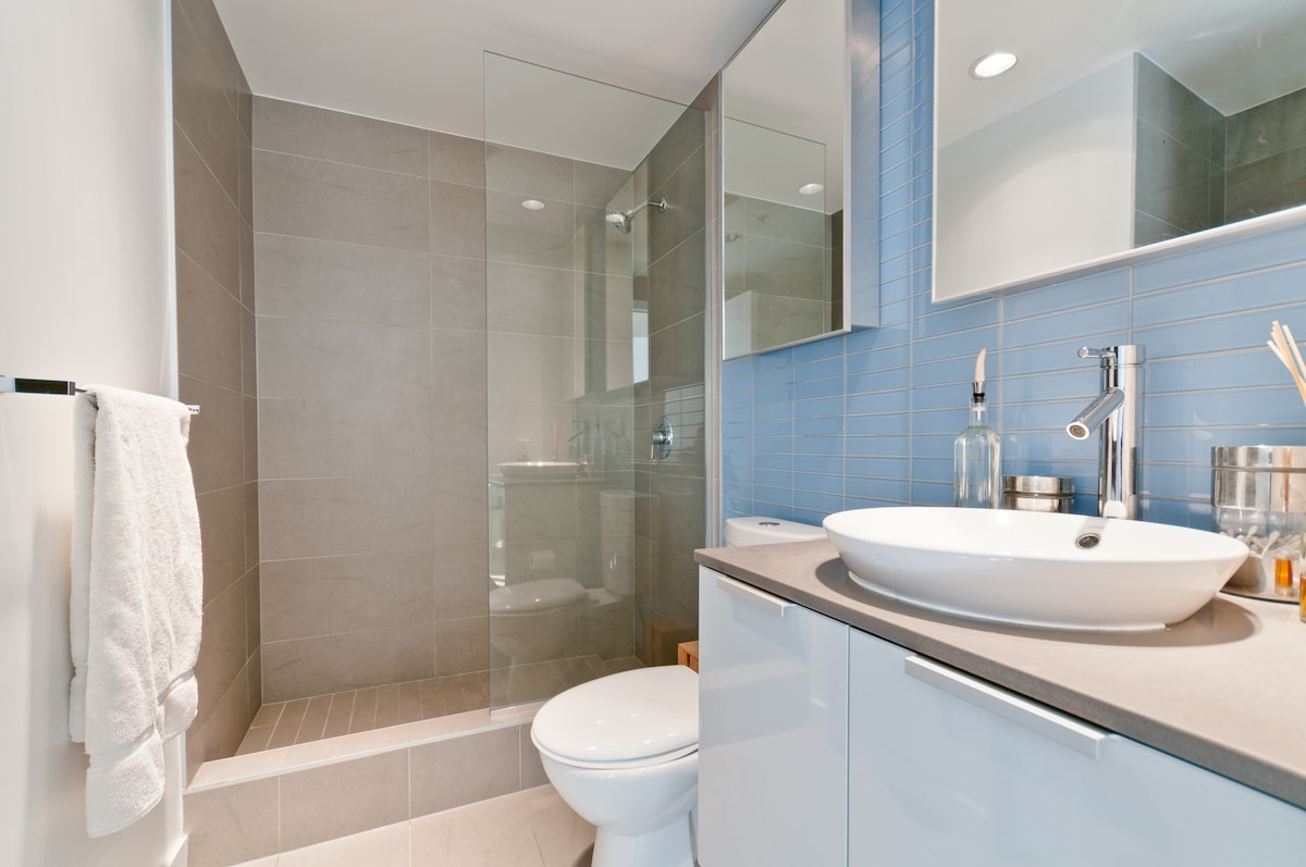 Walk - in shower  complimented with separate his and her vanities