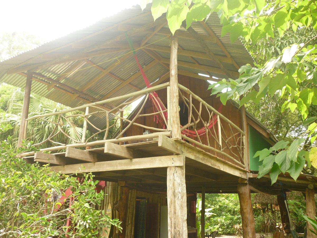 Rear view of cabin. Balcony and bedroom upstairs, kitchen, bathroom and open area downstairs