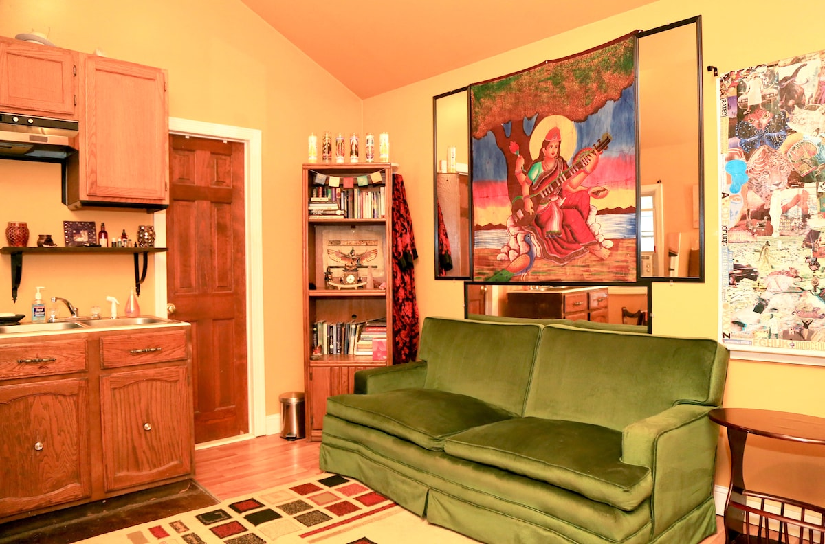 The living area with green velvet antique couch, art, books, and decor made to feel like a temple..
