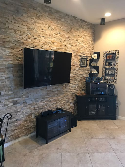 "65"" LED TV on swivel mount so you can watch from anywhere! Colors pop from the rock accent wall"