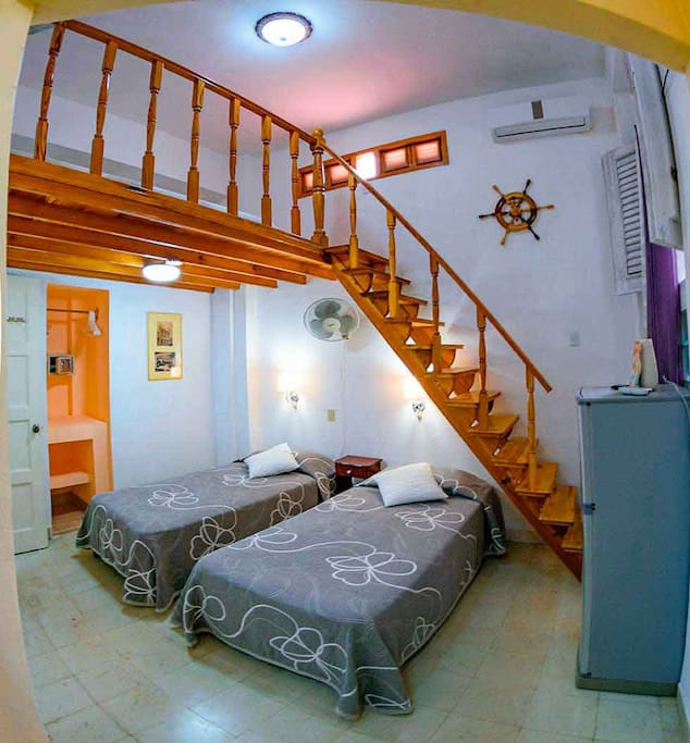 room with two personal beds and double bed in mezzanine