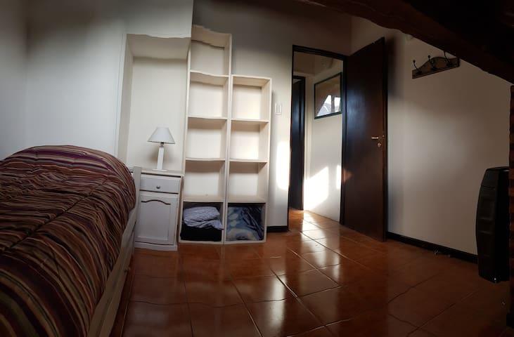 Dormitorio con cama individual y carricama...