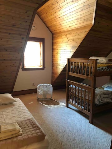 Apartment above the attached garage bedroom with single bunks, and single bed on floor.