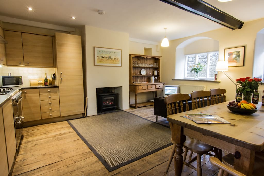 Kitchen with log effect gas fire, large farmhouse table, and 4 oven dual fuel cooker.